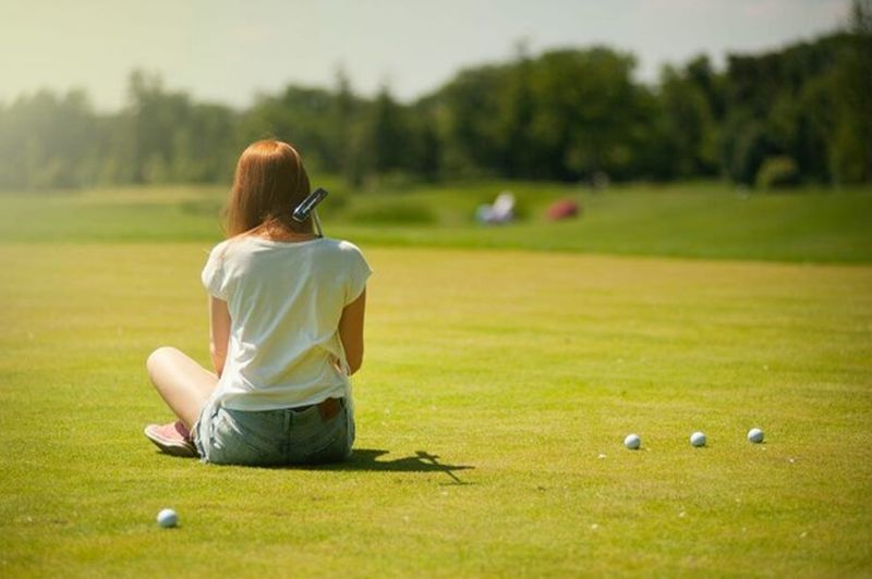 girl sitting on golf course